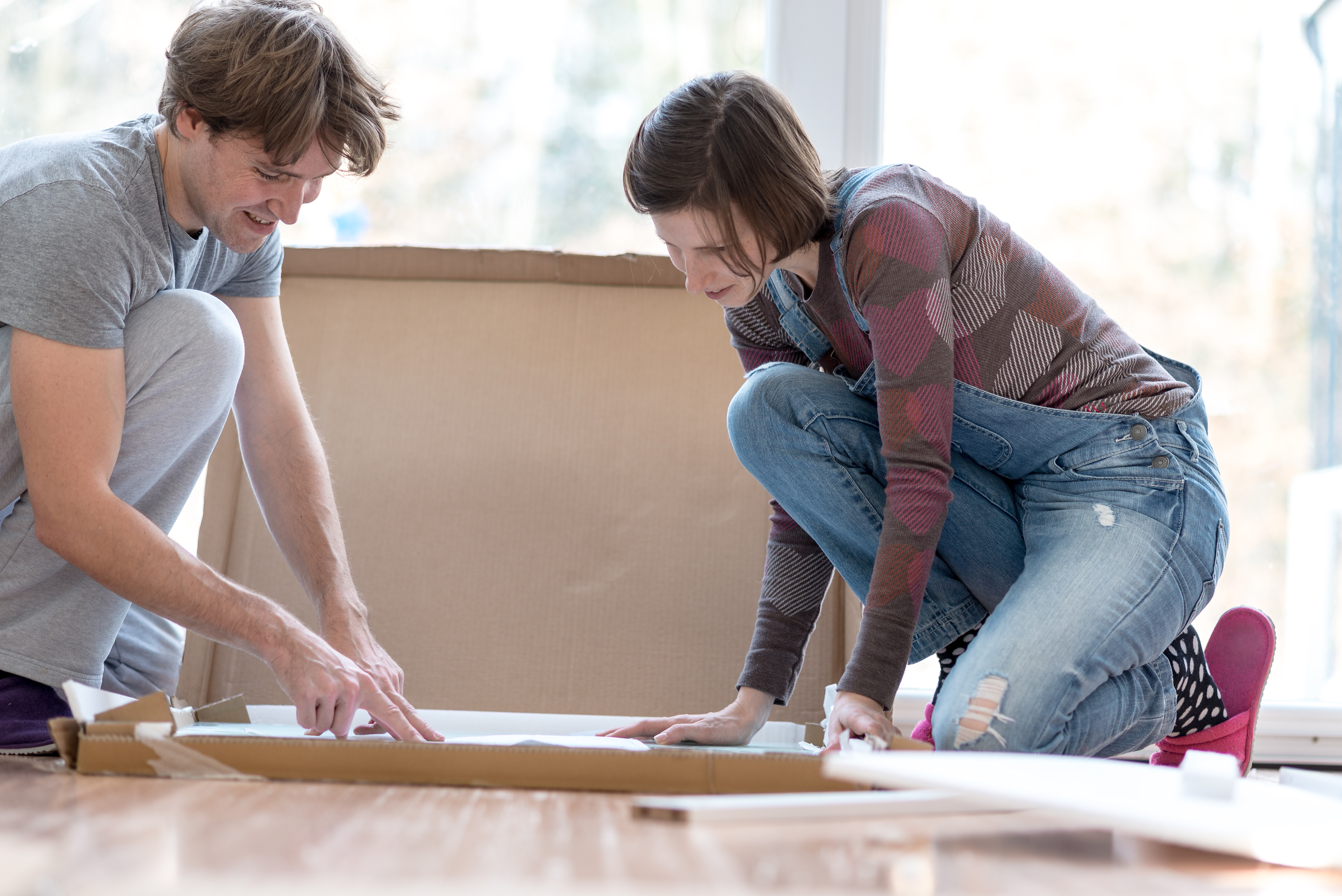 Young couple taking delight in putting together self assembly furniture as they move into their new home.