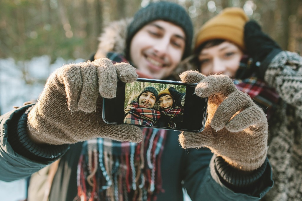 Young hipster couple taking selfie in winter forest with smartphone