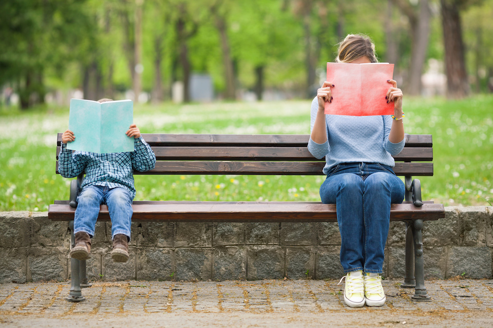 Little boy and his mother sitting on a park bench reading books