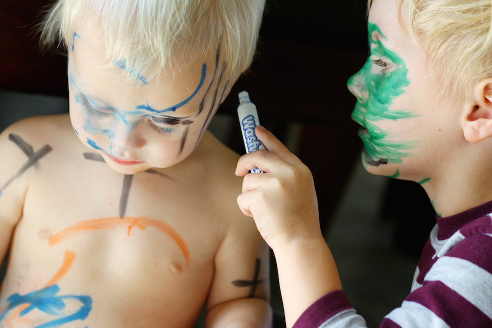 A young child his carefully coloring with a marker all over his baby brother's face and skin